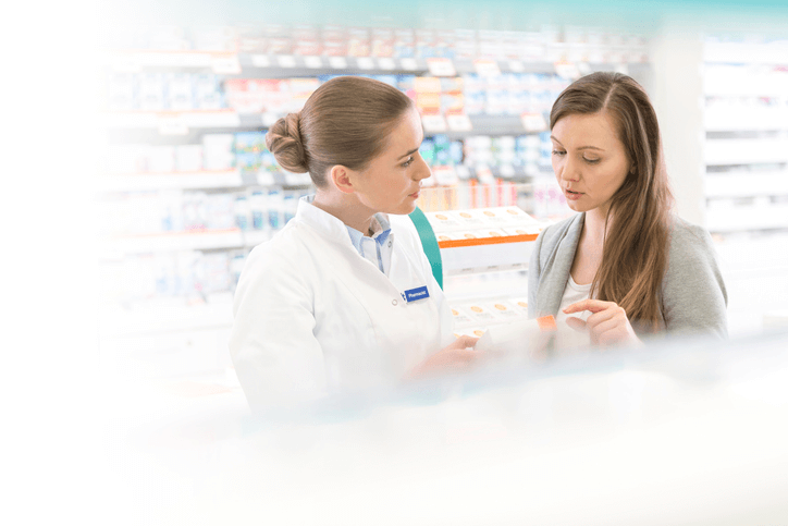 A woman asking a pharmacist about Fleurstat BV treatment gel
